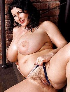 Грудастая голая тетка онанирует на лестнице